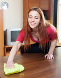 Long-haired woman in red cleaning wooden table. At home Stock Photos