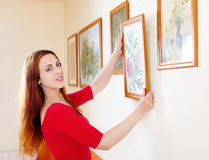 Long-haired woman in red hanging  pictures Royalty Free Stock Image