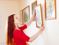 Long-haired woman in red hanging the  pictures Royalty Free Stock Photo