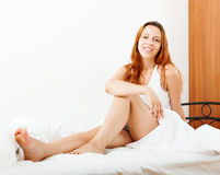 Long-haired woman sitting on  sheet Stock Image