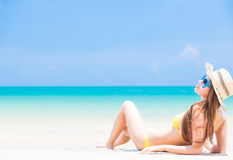 Long haired woman in straw hat in bikini on Stock Photography