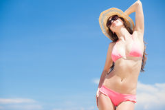 Long haired woman in straw hat in bikini on Stock Images