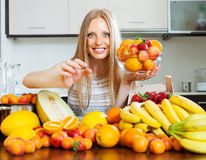 Long-haired woman taking fruits from table Stock Photography