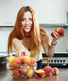 Long-haired woman taking peaches at table Stock Photo