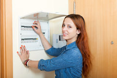 Long-haired woman turning off the light-switch at power control Stock Photo
