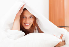 Long-haired woman under white sheet Royalty Free Stock Photography