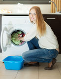 Long-haired woman using washing machine at home Stock Image