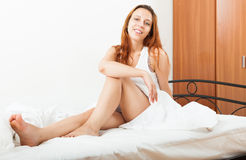 Long-haired woman waking in her bed with white sheets at home Royalty Free Stock Photo