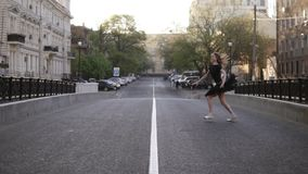 Long haired young ballerina in black ballet tutu jumping cross the empty road in the european street. Ballet movements. Front view. Slow motion stock video