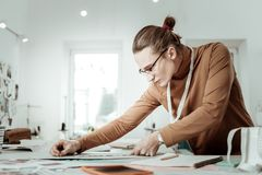 Long-haired young designer from a fashion school in a brown garment looking involved. Measurements. Long-haired young designer from a fashion studio wearing a royalty free stock images
