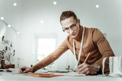 Long-haired young designer from a fashion school in a brown garment making notes. Measurements details. Long-haired young designer from a fashion school wearing stock image