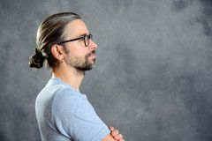 Long haired young man with bun. Looking sideways stock photos