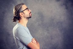 Long haired young man with bun. Looking sideways Royalty Free Stock Images
