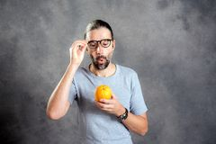 Long haired young man with orange. In front of gray background Royalty Free Stock Images