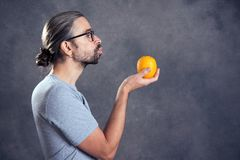 Long haired young man with orange. In front of gray background Royalty Free Stock Photo