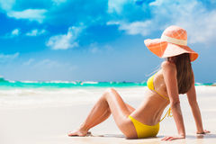 Long haired young woman in bikini and sunglasses on tropical beach Royalty Free Stock Photos