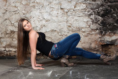 Long-haired young woman at old stone wall. Long-haired young woman sitting at old stone wall royalty free stock photo