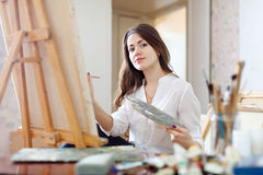 Long-haired young woman paints on canvas. In workshop royalty free stock image