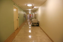 Long hallway in a hospital with a vacant bed Stock Image