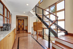 Long hallway interior with polished granite tile flooring. Modern metal staircase and cabinets. Northwest, USA stock image