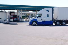Big rig semi truck with dry van trailer on truck stop with gas s. Long haul big rig semi truck with dry van trailer going on truck stop to gas station with stock images