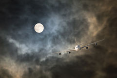 Long-haul night flight through clouds in light of full moon Royalty Free Stock Photography