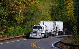 Long haul Semi Truck bulk trailers on autumn winding road Stock Photos