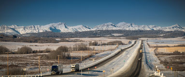 Long haul trucks driving in mountains on highway in winter Stock Images