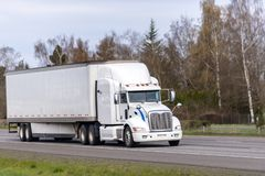 Long haul white big rig semi truck transporting goods in dry van semi trailer running on straight highway road. Long haul professional reliable freight royalty free stock images