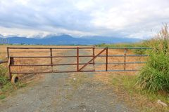 Antique Farm Gate and Scenic Landscape. A long, heavy metal fence is closed to a scenic landscape comprised of snow capped mountains and wide open hay fields royalty free stock images