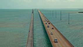 A long highway bridge crossing the ocean with traffic moving both directions stock video