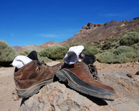After a long hike in the mountains. Boots and socks shot after a hike to the mountain edge in the background of the picture, volcanic area at tenerife, spain Royalty Free Stock Photography