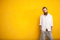 Long hippie barbu sur le mur jaune photo stock