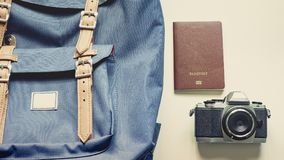 Long holiday travel flat lay concept from blue backpack and lath. Er strap for man with retro camera and passport put on isolated white background Royalty Free Stock Photos
