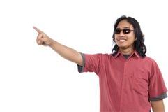 Long homme de cheveu avec des lunettes de soleil dirigeant quelque chose photo stock