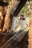 Long homme de cheveux dans le blanc derrière l'arbre Image stock