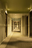 Long hotel corridor with doors and elevator. Atmospheric hotel corridor with doors Stock Photo
