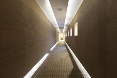 Long hotel corridor with modern floor and ceiling lights Stock Photo