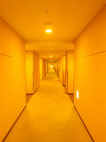 Long hotel corridor with warm light Stock Images