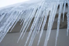 Long icicles dangle from the roof in winter stock photos