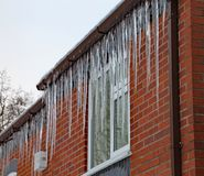Long icicles hang from the gutter of a house. The roof is covered in snow and it`s still snowing stock photo