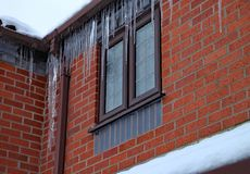 Long icicles hang from the gutter of a house. The roof is covered in snow and it`s still snowing stock photography
