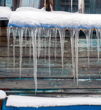 Long icicles hanging from the roof of  house. Stock Image