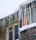 Long icicles hanging from the roof of  house. Royalty Free Stock Photos