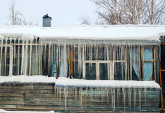 Long icicles hanging from the roof of  house. Stock Images