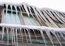 Long icicles hanging from the roof of  house. Stock Photos