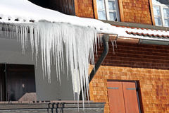 Long icicles at an old house. In winter Stock Photo