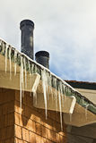 Long Icicles. Icicles slowly melt due to the morning sunlight.  To add, light snow blows this cold morning seen in both the foreground and background Stock Photography