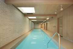 Long indoor swimming pool. With wood ceiling beams Royalty Free Stock Photo