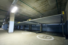 Long indoor two-level parking with electrolifts. And concrete floor for many cars Stock Image
